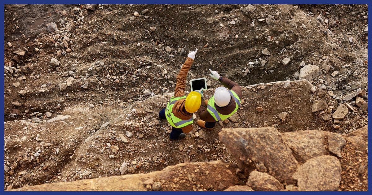 Dois trabalhadores utilizam sistema digital para avaliar trabalho de geotecnia